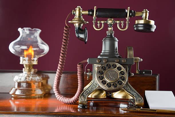 altmodische telefon und öl-lampe - telefonschrank stock-fotos und bilder