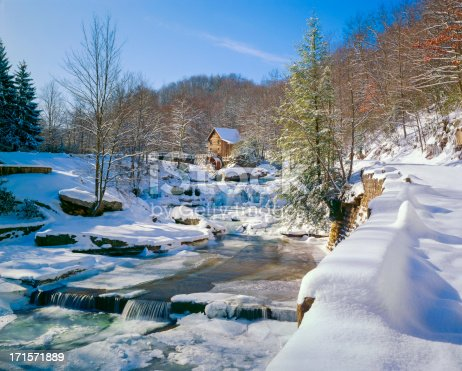 A fresh blanket of snow on a nostalgic old-fashioned gristmill and stream in a pubic state park - sunny winter day at Glade Creek Grist Mill in Babcock State Park, West Virginiamore winter and snow: