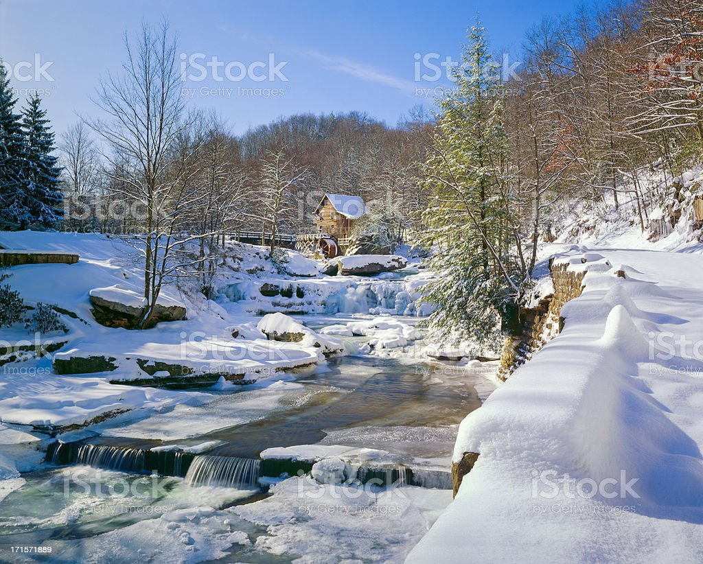 old-fashioned watermill gristmill and stream in snow stock photo