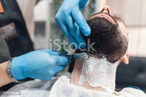 Professional barber wet shaving and trimming young man's beard
