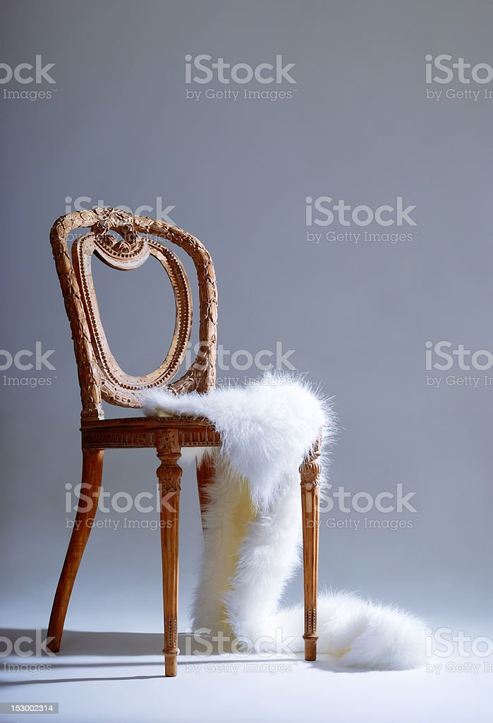Old-fashioned wooden chair with white fur royalty-free stock photo
