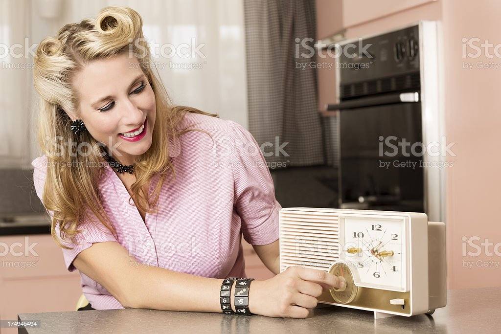 Old-fashioned young woman listening to the radio in the old-fashioned...