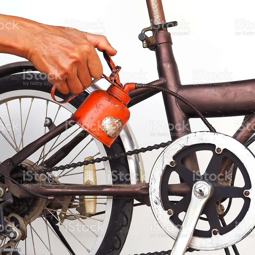 Oldman use oiler to chain of bycicle. stock photo