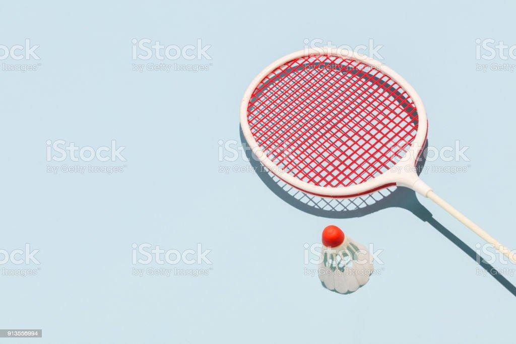 Oldschool racket and birdie on blue background royalty-free stock photo