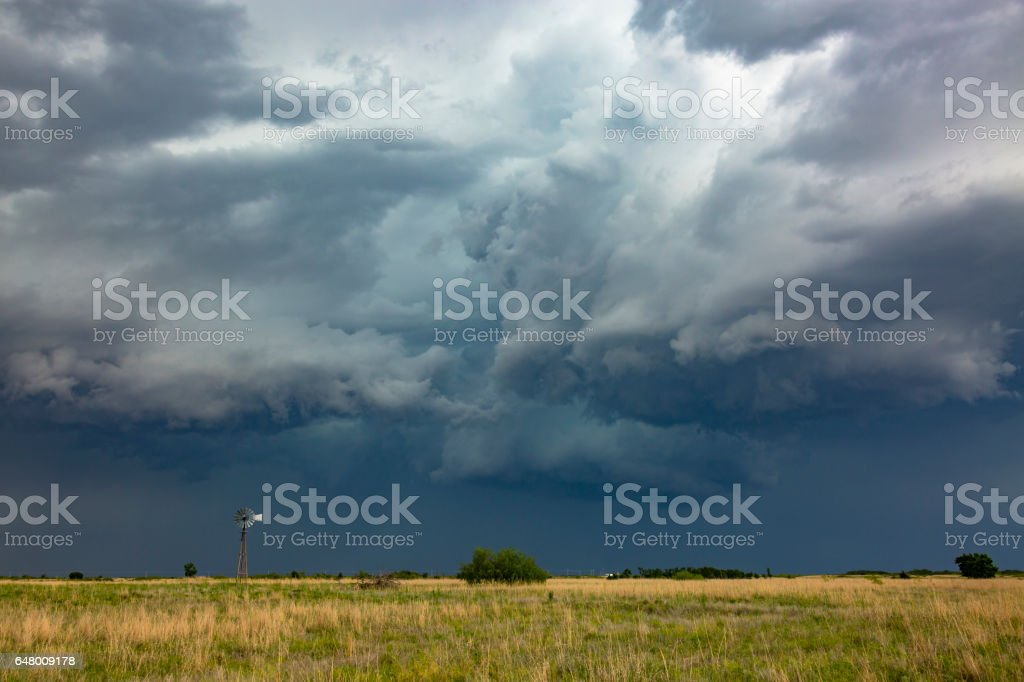 Old-style windmill dwarfed by severe, dangerous thunderstorm stock photo