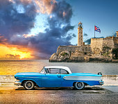 Oldtimer vintage car in front of Faro Castillo del Morro lighthouse located in Havana Cuba at sunset