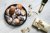 istock oliebollen, oil dumpling or fritter. traditional treat for Dutch New Year's Eve. with champagne and present 1072679456