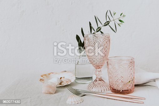 Olive  brunch and pink glasses on  linen tablecloth Minimalistic table decorated background