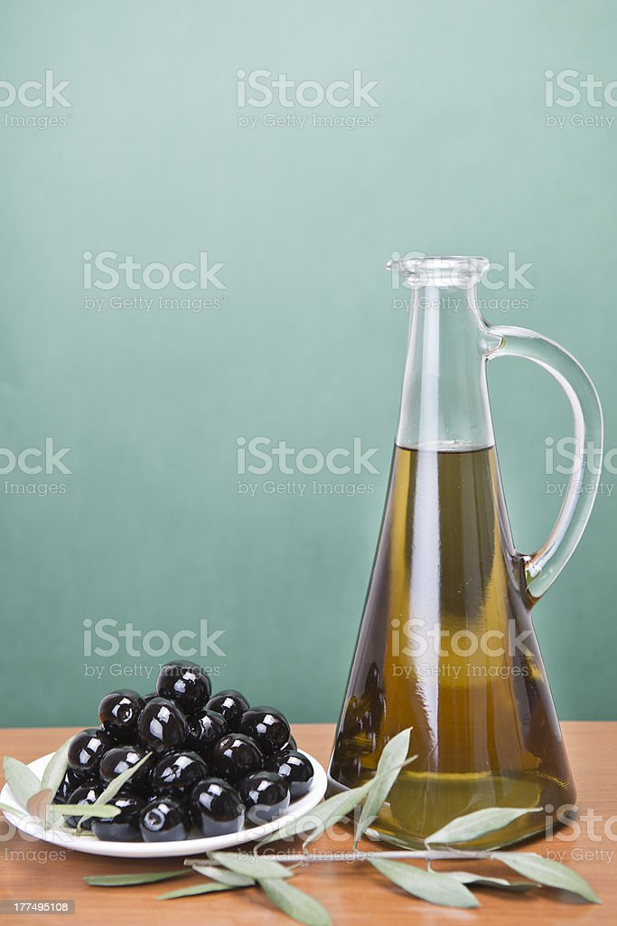Olive oil and a plate with black olives. royalty-free stock photo