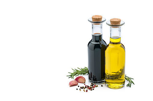 Olive oil and balsamic vinegar bottles isolated on reflective white background