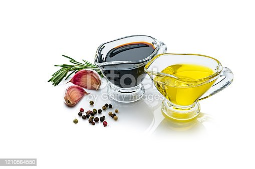 Extra virgin olive oil and balsamic vinegar in glass gravy boats isolated on reflective white background. Rosemary twigs, garlic cloves, and mixed peppercorns are around the containers and complete the composition. The composition is at the right of an horizontal frame leaving useful copy space for text and/or logo at the left. Predominant colors are yellow, black and white. High resolution 42Mp studio digital capture taken with Sony A7rII and Sony FE 90mm f2.8 macro G OSS lens
