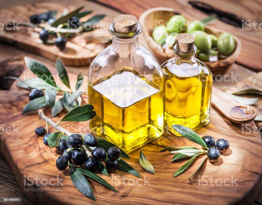 Aceite de oliva y frutos están en la bandeja de madera de olivo. - foto de stock