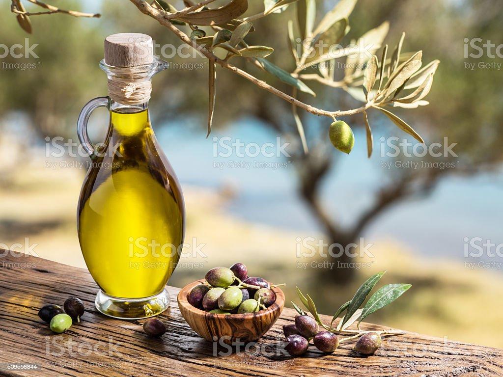 Azeite de oliva e frutas silvestres estão sobre a mesa de madeira. - foto de acervo