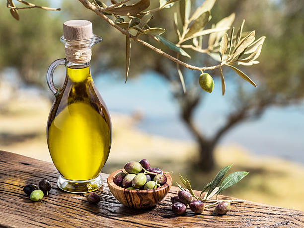 Olive oil and berries are on the wooden table. Olive oil and berries are on the wooden table under the olive tree. olive oil stock pictures, royalty-free photos & images