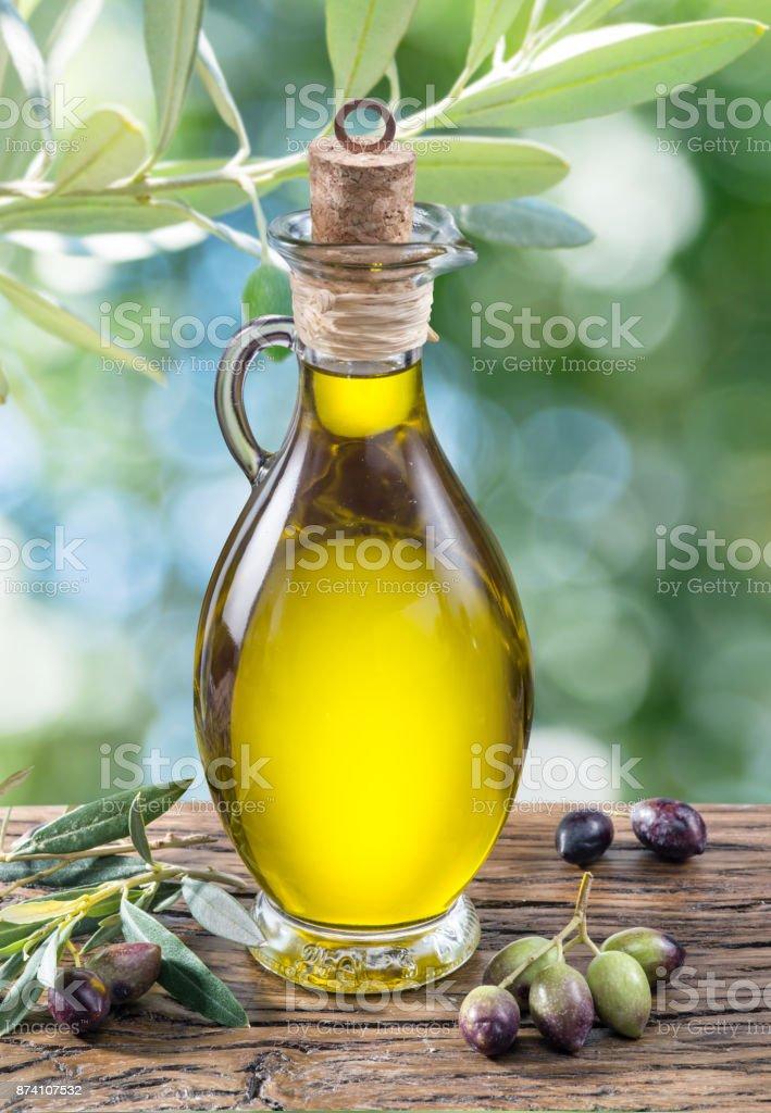 Aceite de oliva y bayas se encuentra en la mesa de madera. - foto de stock