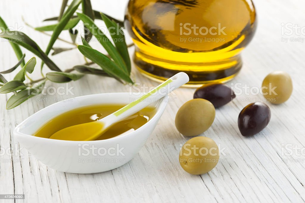 Olive oil and green and black olives on white stock photo