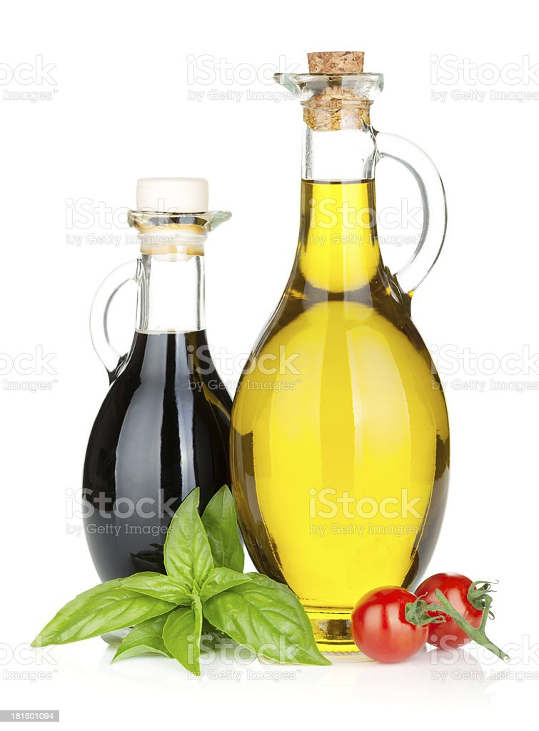 Olive oil and vinegar displayed with tomato and basil royalty-free stock photo