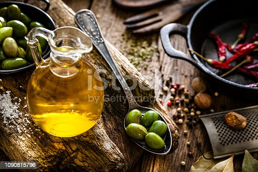 High angle view of an olive oil bottle and green olives in an vintage metal spoon shot on rustic wooden table. A cast iron pan, grater, and wooden kitchen utensils as well as some spices are out of focus at background.  Predominant colors are brown and gold. Low key DSRL studio photo taken with Canon EOS 5D Mk II and Canon EF 100mm f/2.8L Macro IS USM.