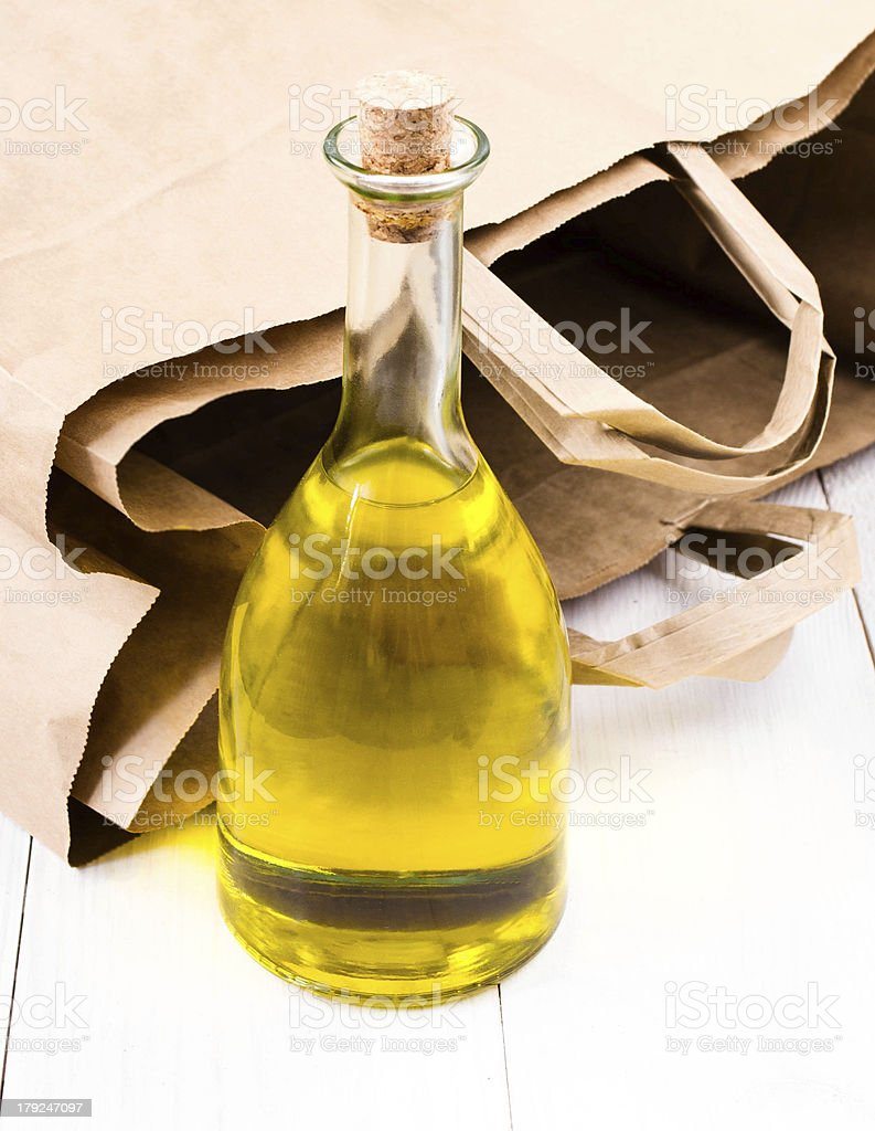 Olive oil bottle and  Paper bag on white wooden  background royalty-free stock photo