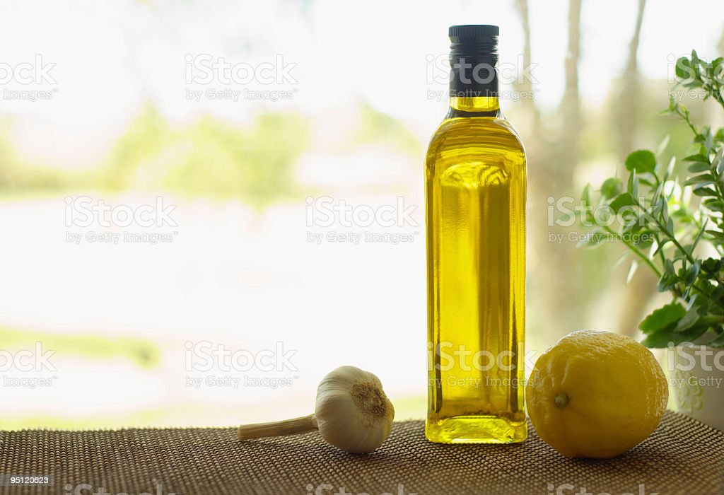 Olive oil bottle with garlic and lemon stock photo