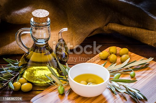 Front view of an olive oil bottle surrounded by green olives and a olive wooden cutting board with more green olives, olive branches and a withe bowl filled with three green olives and olive oil on top. Low key DSLR photo taken with Canon EOS 6D Mark II and Canon EF 24-105 mm f/4L