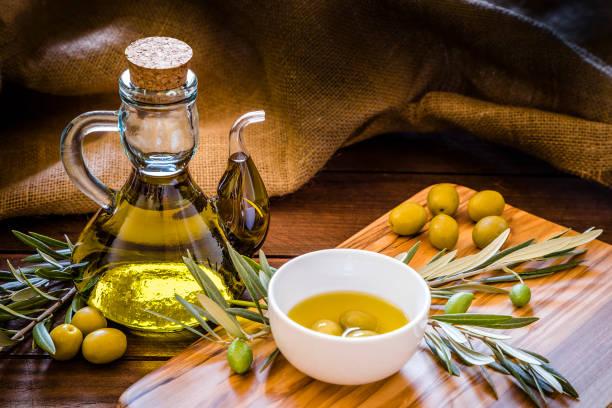 olive oil bottle with olive branch on a olive wooden cutting board with copy space - olive oil  - stock snímky, obrázky a fotky