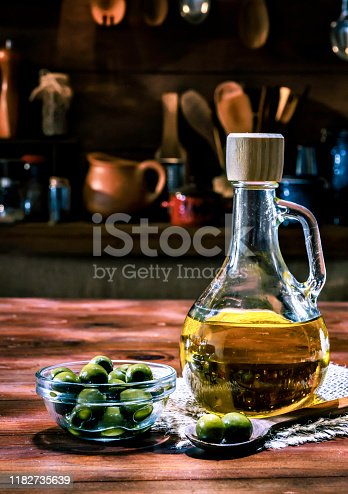 Olive oil bottle with olives. Arrange on table in old fashioned rustic kitchen.