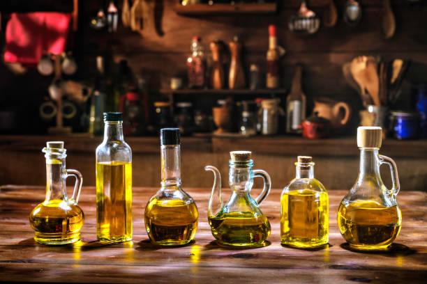 olijfolie flessen collectie op houten tafel in een ouderwetse keuken met lage sleutel verlichting - oil kitchen stockfoto's en -beelden