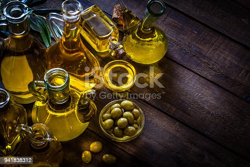 High angle view of various olive oil bottles shot on rustic wood table. A glass bowl filled with green olives complete the composition. An olive tree branch is at the left-top corner. The composition is at the left of an horizontal frame leaving useful copy space for text and/or logo at the right. Predominant colors are gold, green and brown. Low key DSRL studio photo taken with Canon EOS 5D Mk II and Canon EF 100mm f/2.8L Macro IS USM
