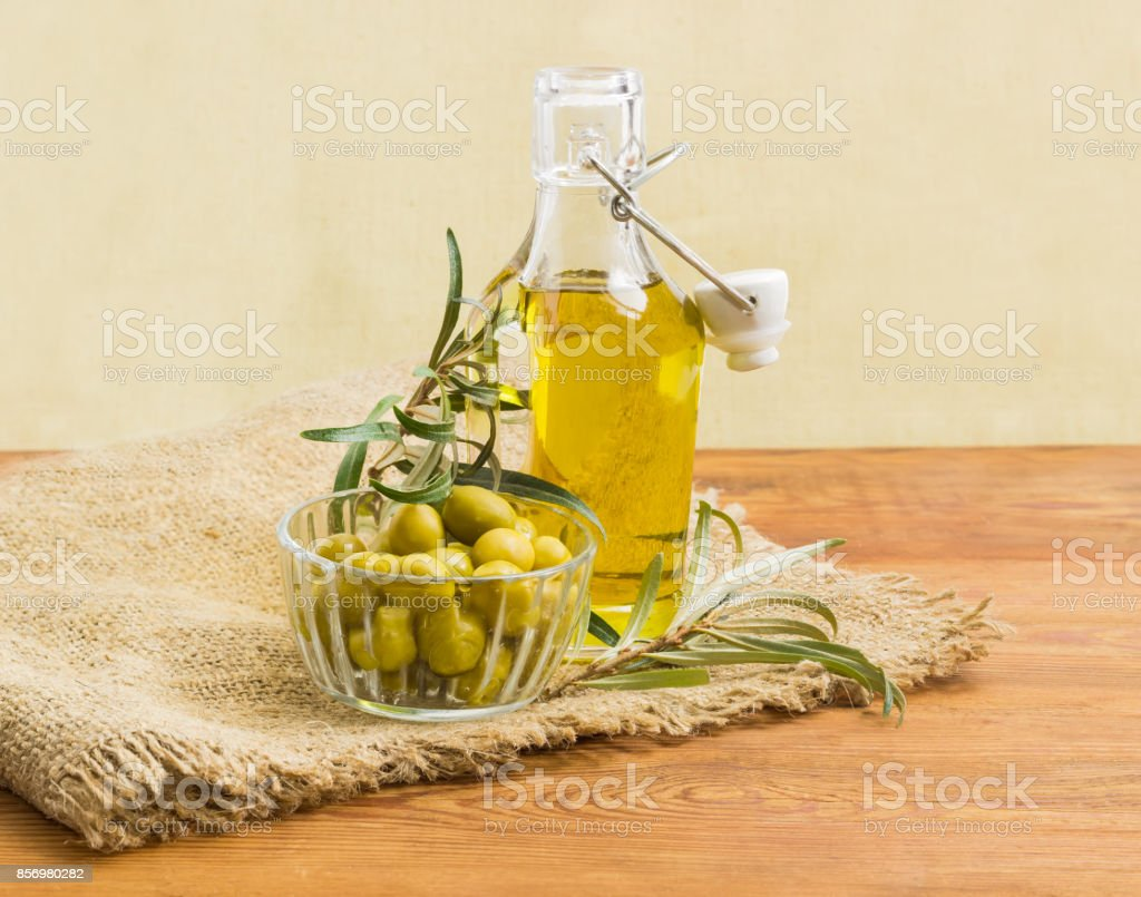 Olive oil, green olives and olive branches stock photo