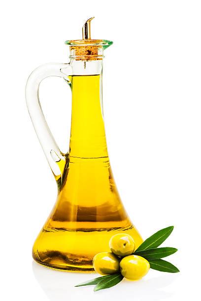 Aceite de oliva en un frasco de vidrio y de aceitunas aislado - foto de stock