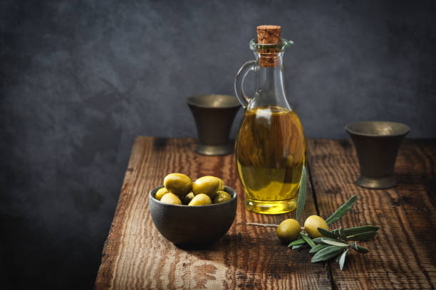 Olive oil in a glass bottle, fresh green olives in a ceramic bowl and olive branch on an old wooden table. Dark background. stock photo