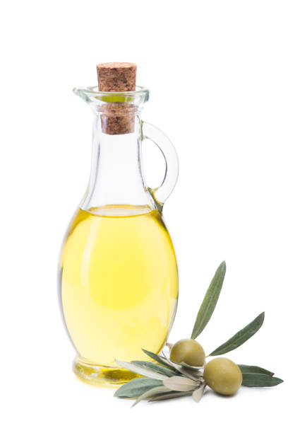 Olive oil in a glass bottle, fresh olives and olive branch. isolated white background. stock photo