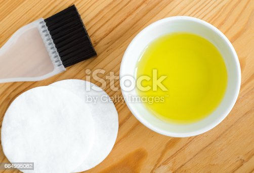 Olive oil in a small ceramic bowl for preparing homemade spa face and hair masks. Ingredients for diy cosmetics.