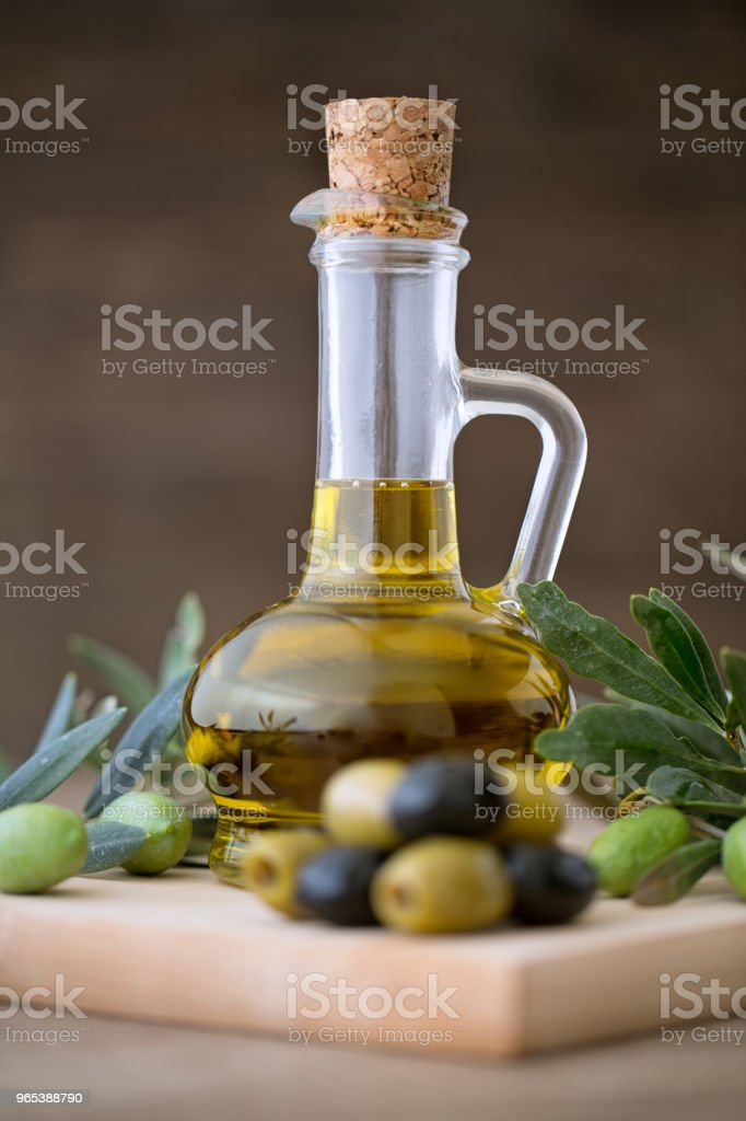 Olive oil in bottle on the wooden table royalty-free stock photo
