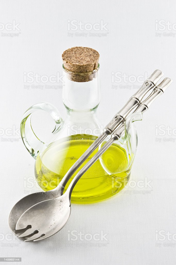 Olive oil in bottle with spoon and fork royalty-free stock photo