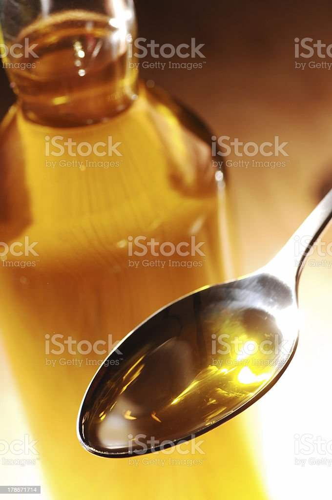 Olive Oil on a spoon, bottle in the background royalty-free stock photo