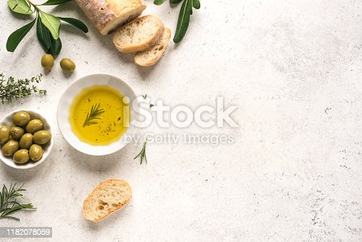 Olive Oil and Bread. Organic olive oil with green olives in bowl, herbs and ciabatta bread on white background with copy space, healthy mediterranean food concept.