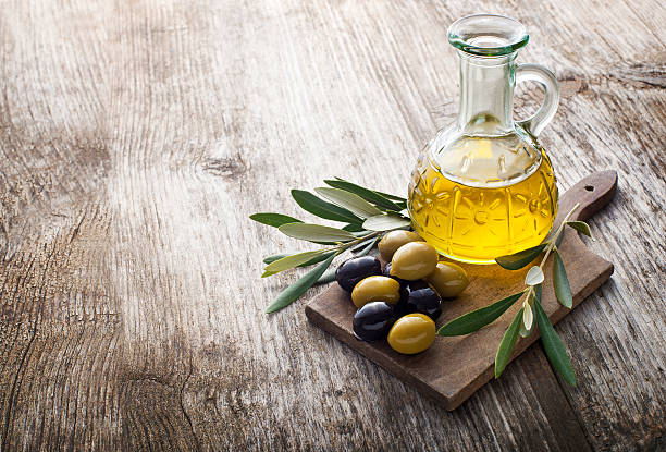 Olive oil Olive oil and olive branch on the wooden table olive oil stock pictures, royalty-free photos & images