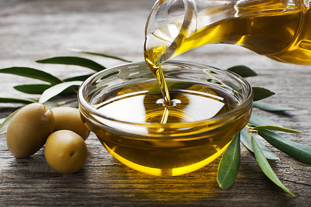 Olive oil Bottle pouring virgin olive oil in a bowl close up olive oil stock pictures, royalty-free photos & images