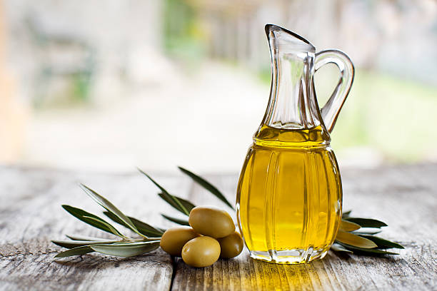 Olive oil Olive oil and olive branch on the wooden table outside olive oil stock pictures, royalty-free photos & images