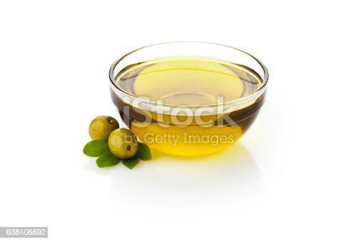 Olive oil and green olives with leaves in glass bowl sitting on reflective white backdrop.  DSRL studio photo taken with Canon EOS 5D Mk II and Canon EF 70-200mm f/2.8L IS II USM Telephoto Zoom Lens