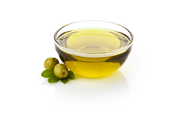 Olive oil Olive oil and green olives with leaves in glass bowl sitting on reflective white backdrop.  DSRL studio photo taken with Canon EOS 5D Mk II and Canon EF 70-200mm f/2.8L IS II USM Telephoto Zoom Lens olive oil stock pictures, royalty-free photos & images