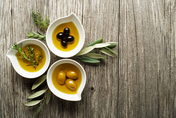 Olive oil Olive oil with fresh herbs on wooden background olive oil stock pictures, royalty-free photos & images