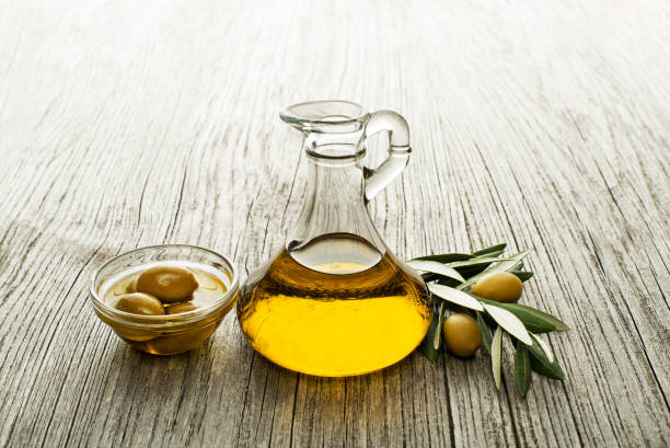 Olive oil Olive oil and olive branch on wooden table olive oil stock pictures, royalty-free photos & images
