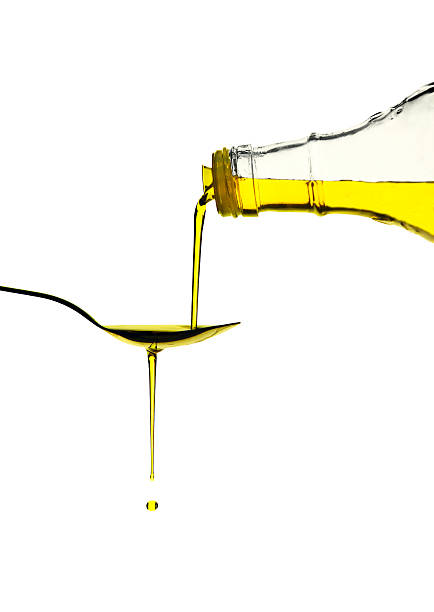 Olive Oil Pouring over a spoon stock photo