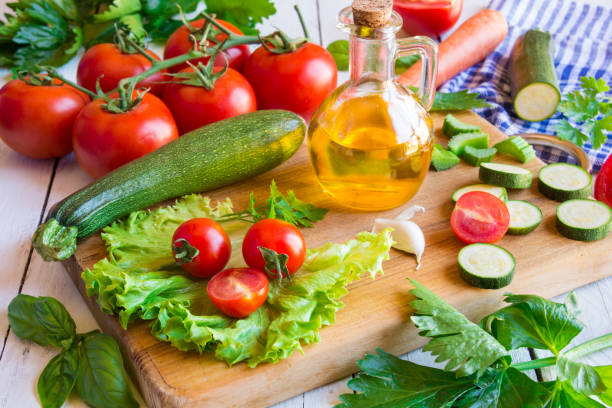 Olive oil, tomato and other cut vegetables stock photo
