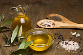 Olive oil, two wooden spoon with salt and pepper on a wooden table