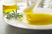 Healthy olive oil with herbs pouring with spoon close up