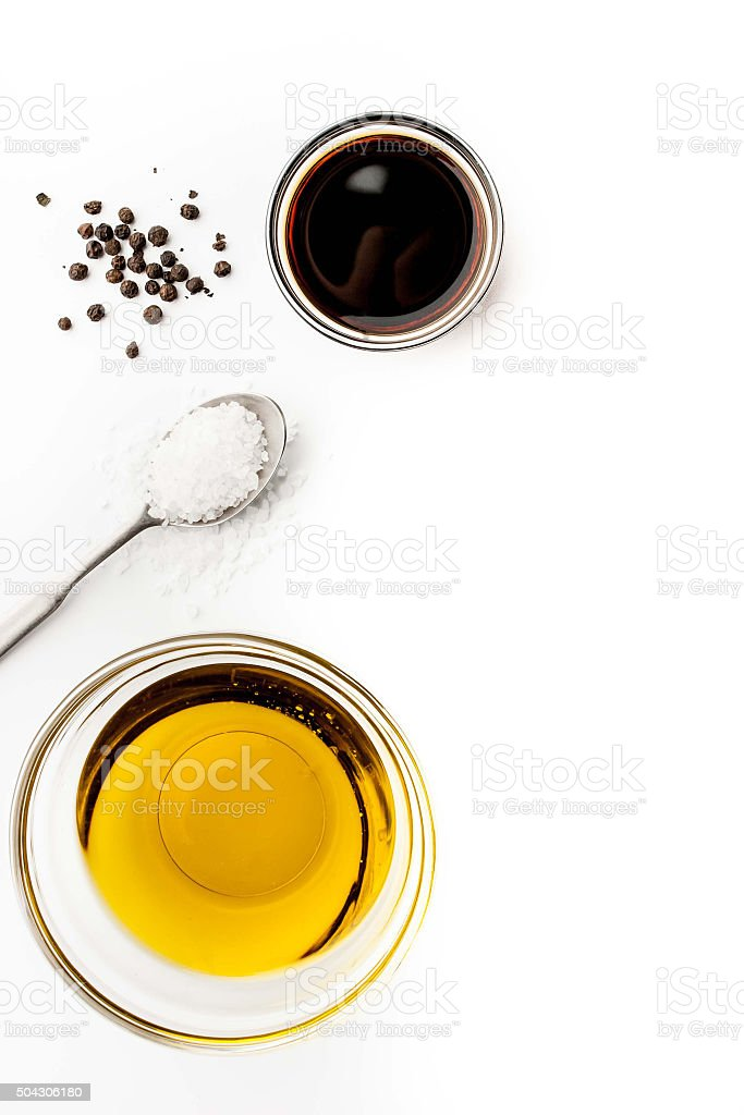 Olive oil with seasoning on the white background vertical stock photo